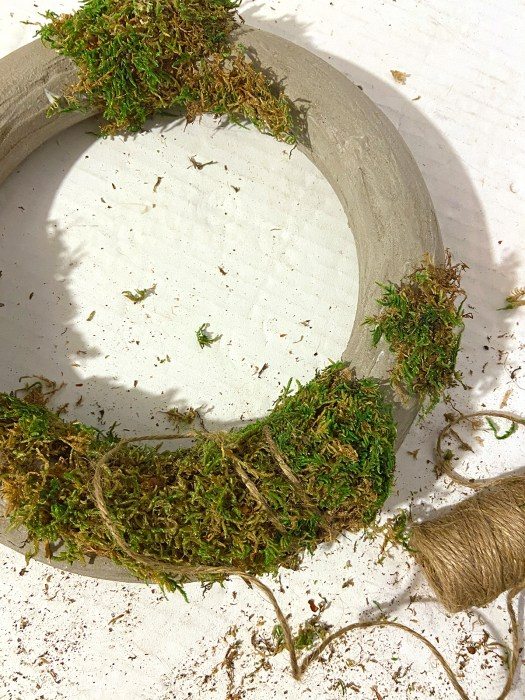 concrete wreath partially covered in moss with a roll of twine lying next to it