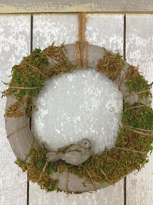 Concrete and moss wreath with a concrete bird in the middle of it