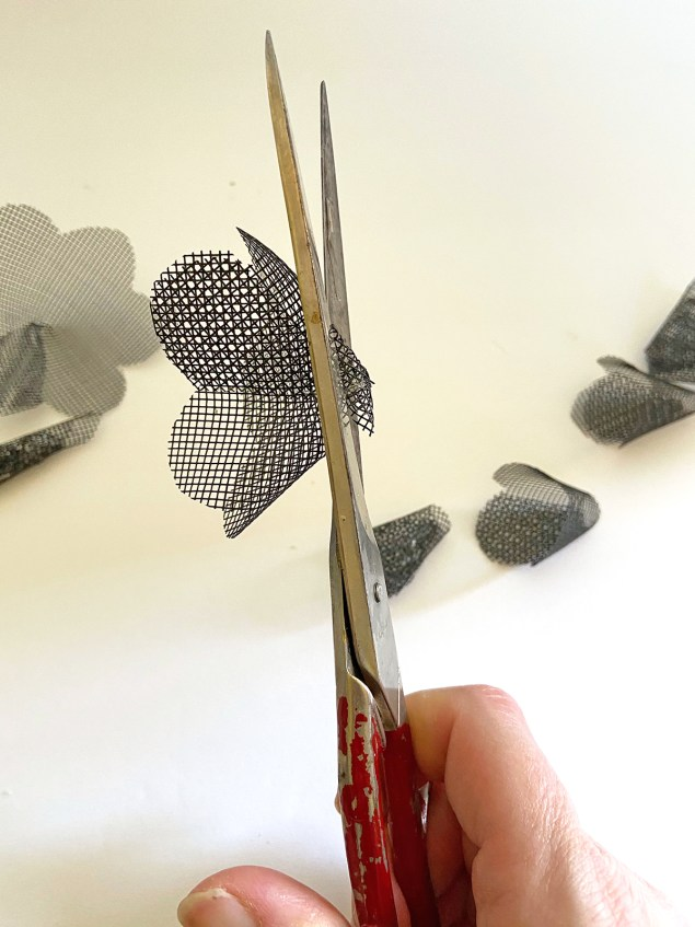 scissors snipping off the bottom of a black mesh cone