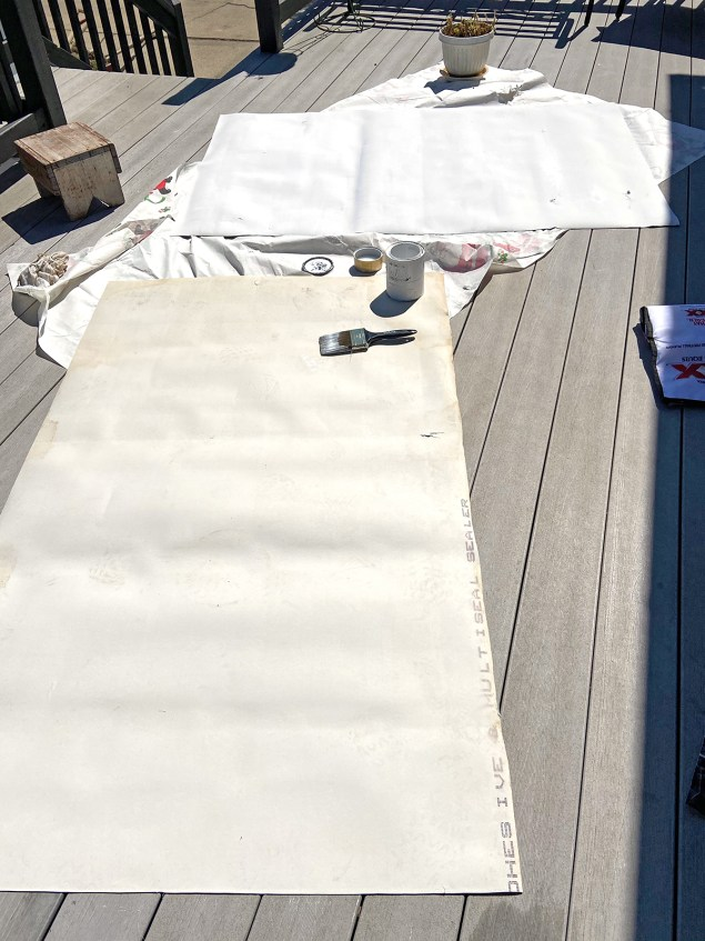 two sections of vinyl flooring; one has a fresh coat of white paint on it, the other is still waiting to be painted