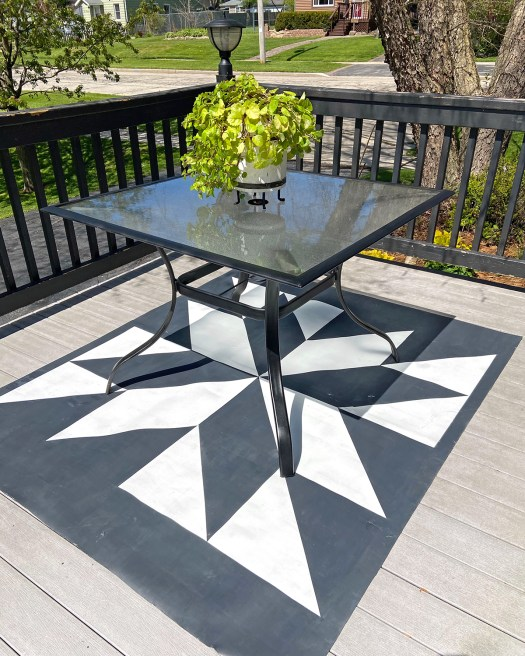 black and white barn quilt patio rug on a deck with a patio table sitting on it