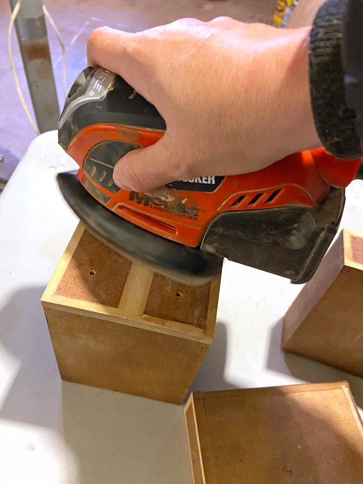 Woman's hand pushing electric sander over small wooden drawers as part of a jewelry box makeover