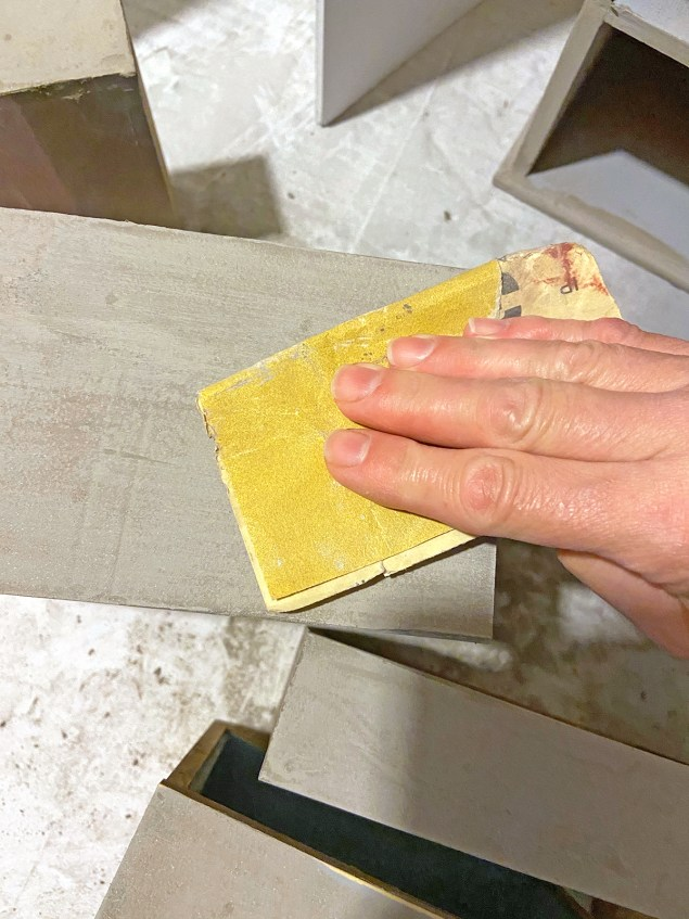 woman's hand holding sandpaper and rubbing it across drawer fronts