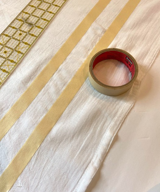 laying tape lines down on dishtowel for chalk paint