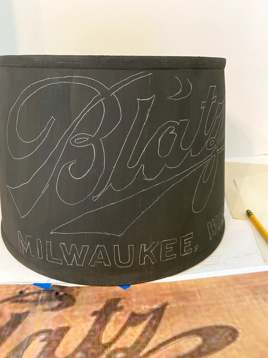 black lampshade with logo outlines transferred in white