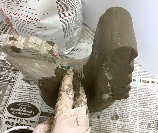 Applying second coat of cement to DIY concrete garden statue