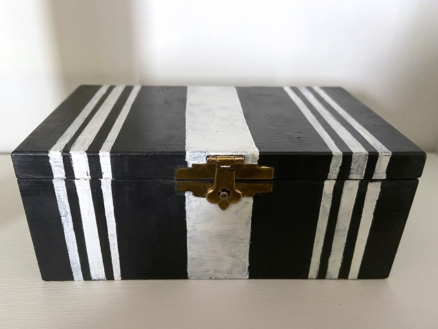 Cedar box after makeover with black and white stripes on it