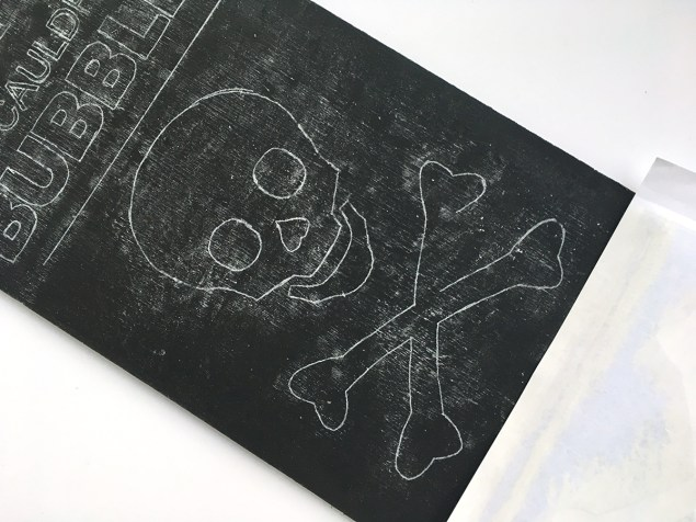 chalk outlines of skull and cross bones for Halloween sign