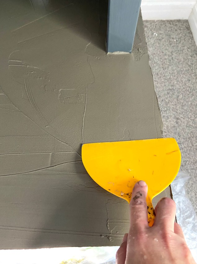 applying the cement skim coat with a plastic spatula