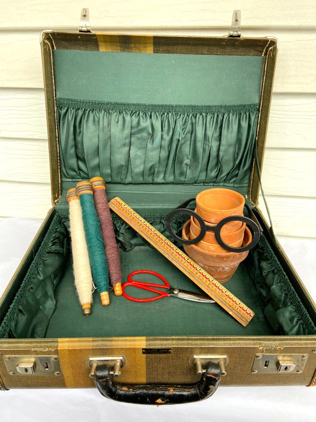 thrift haul; vintage suitcase with wooden spools, red handled scissors, and old ruler in it