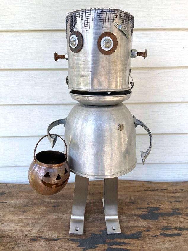 Robot Frankenstein assemblage holding a jack-o-lantern.