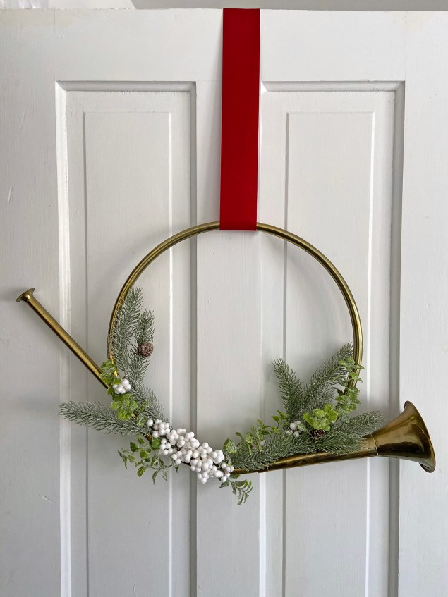 vintage brass French horn wreath hanging from a red velvet ribbon