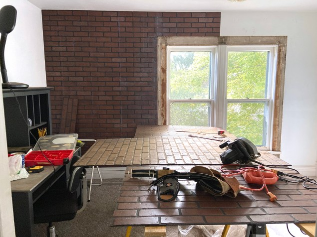 wall with faux brick paneling partially hung