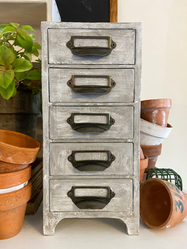 concrete apothecary cabinet surrounded by terra cotta planters