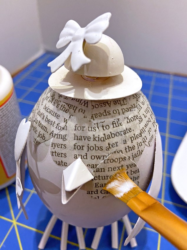 decoupaging newspaper hearts onto Easter chick