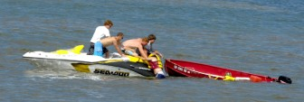 Two boaters in life jackets are aided by passing boaters July 10 near Racine on Lake Michigan, where a sheriff's official said the small motorized craft was capsized by the wake from larger boats near the city's main harbor.