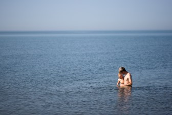 Andrew Harvey plays with his daughter in Lake Superior in July 2012. Economic development leaders in northern Wisconsin say tourism is an economic boost to the area, but the state does not offer financial assistance to tourism, retail, or hospitality businesses.