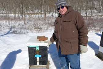 Farmer and beekeepr Harriet Behar stands with one of the 25 beehives she maintains on her farm in Crawford County. She would prefer Wisconsin to draw up a tougher plan for protecting bees, butterflies and other pollinators that would discourage pesticide use.