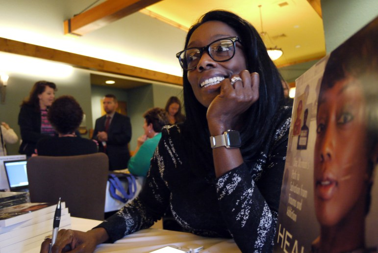 Tonier Cain signs copies of her autobiography, 'Healing Neen,' during a statewide conference in the Wisconsin Dells, Wis., on using trauma-informed care to help children overcome adverse childhood experiences. A former homeless crack addict, Cain travels the world advocating the use of trauma-informed care to help children and adults heal from negative experiences.