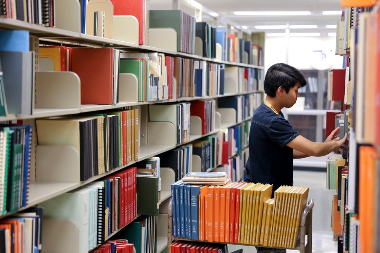 Marvin Vergara Jr. shelves books at Arizona State University's library in Tempe. Arizona is among the states where college student IDs are not valid for voting.