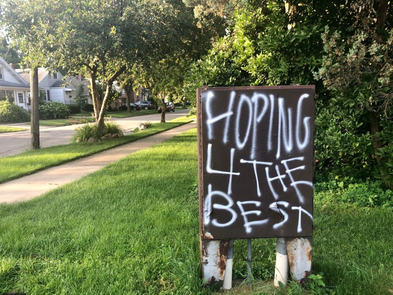 """A spray-painted sign in Madison reads: """"HOPING FOR THE BEST"""""""