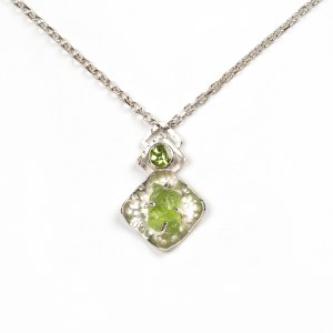 Handmade peridot pendant set in sterling silver with faceted peridot and peridot crystal