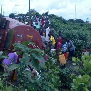 PHOTOS: Nigerians Risk Their Lives Just to Scoop Fuel From A Tanker Rammed into Police Van in Uyo