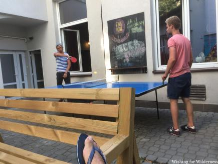 Two people playing table tennis in a hostel