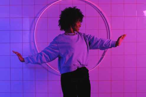 stylish black woman standing with raised arms in room with neon lights in room with neon lights