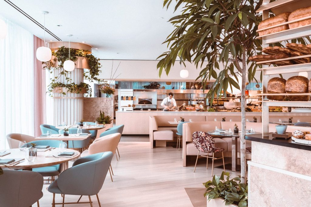 Bright and spacious restaurant dining space with pink and blue chairs and plants