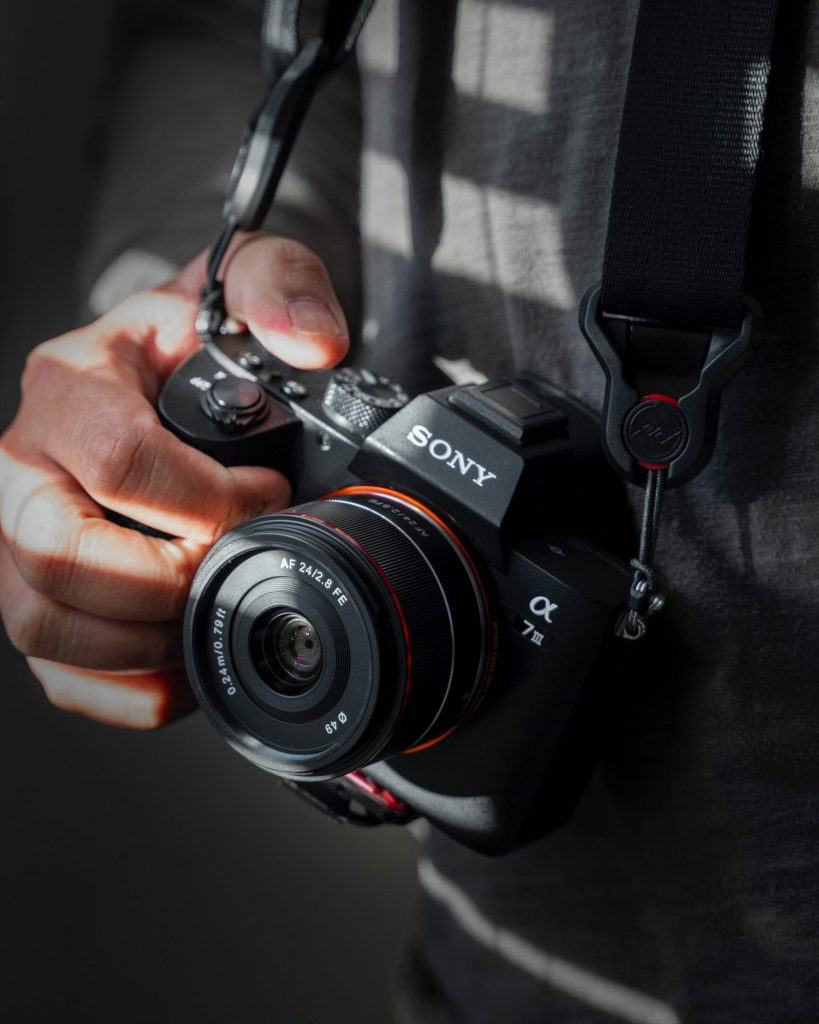photo of black sony camera held in hand