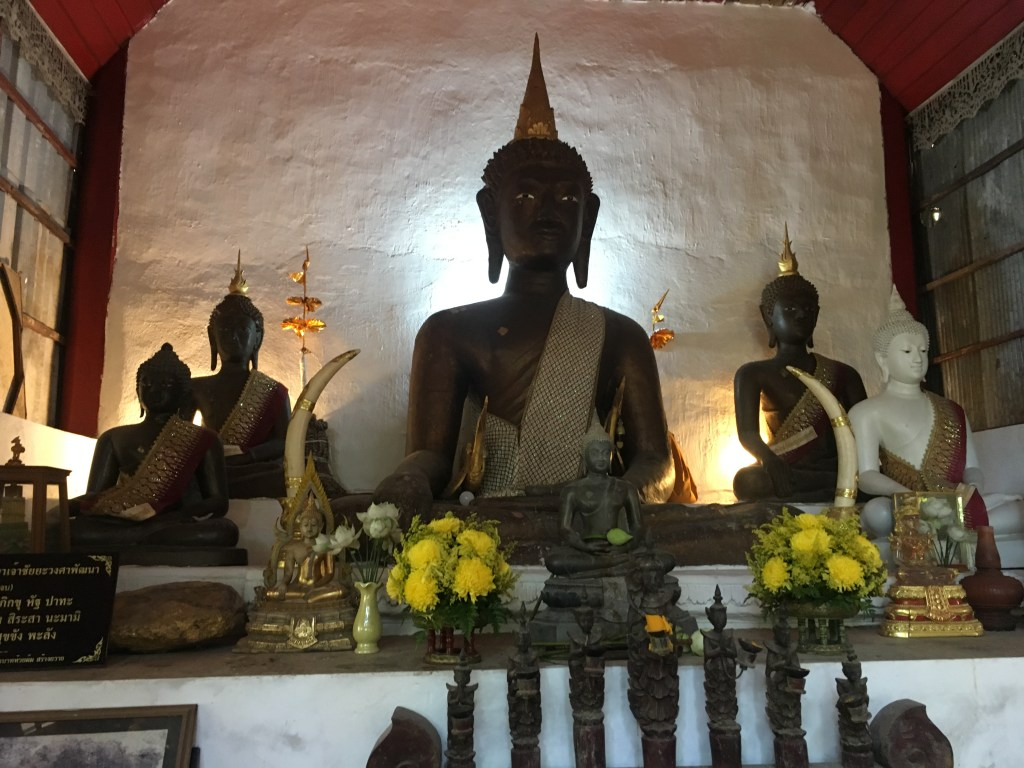 Buddha statues and offering at Wat Pha Lat, a temple in the mountains of Chiang Mai, Thailand.
