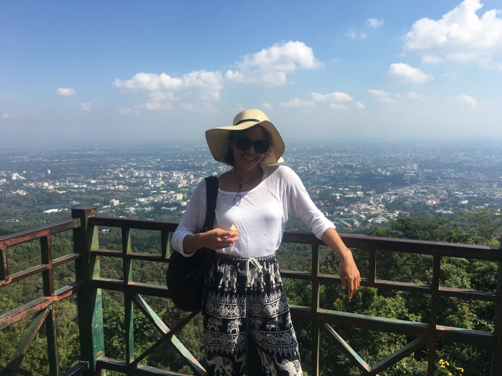 A photo of myself at another beautiful viewpoint of rolling mountains and blue skies in Chiang Mai, Thailand.
