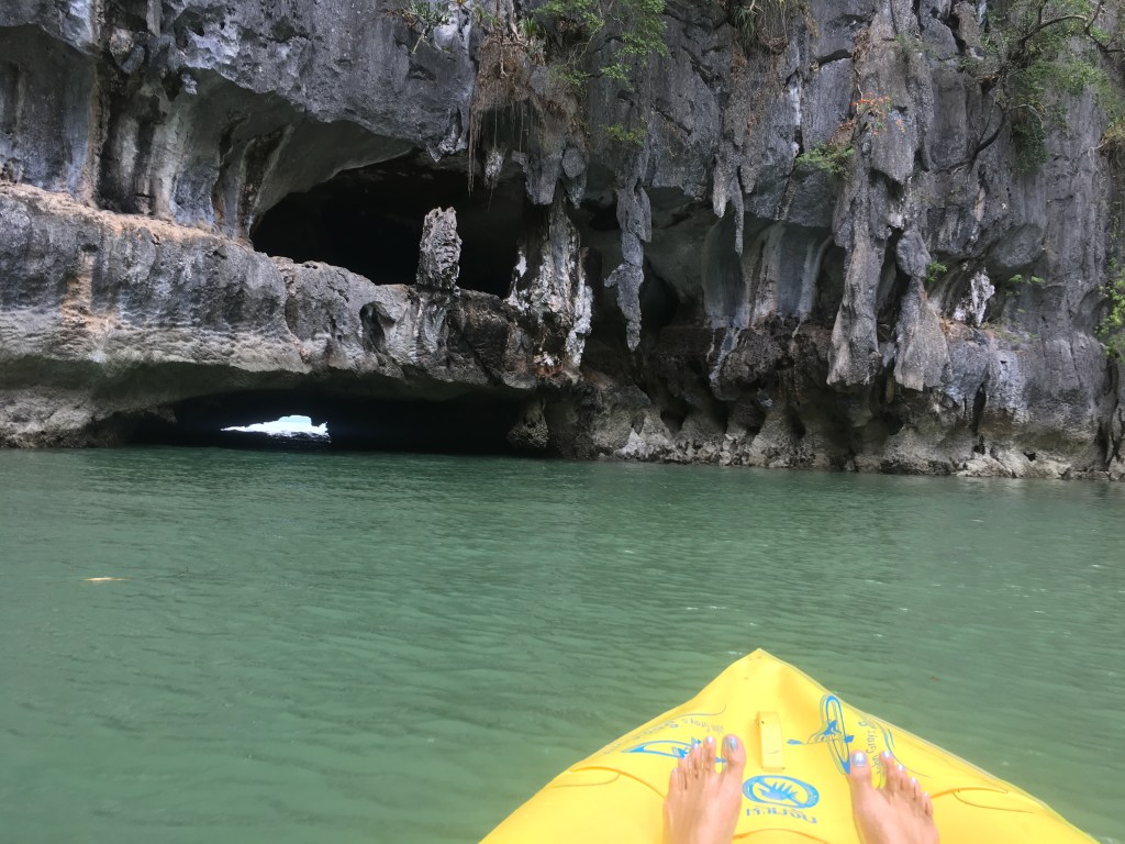 Yellow kayak approaching a cavern in Phang Nga Bay, Thailand.