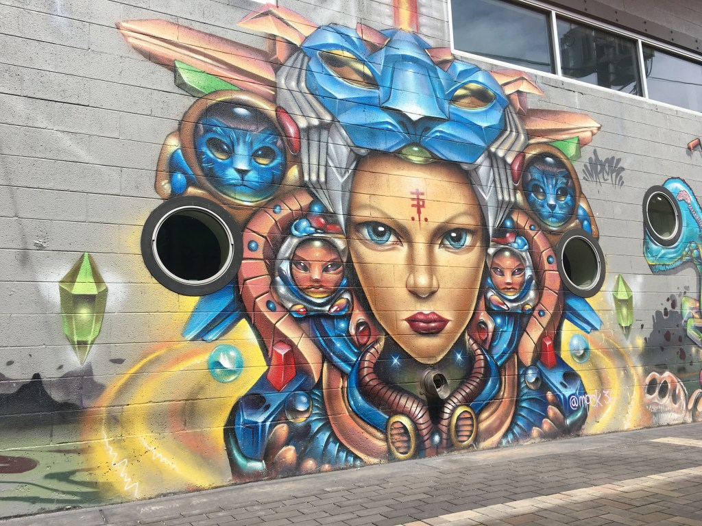 Surreal graffiti of woman's face with religious-looking headdress that has futuristic elements involving cats. RiNo arts district in Denver, Colorado.