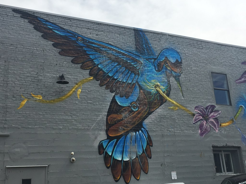 Cool graffiti of a blue bird and flower vine in RiNo arts district. Denver, Colorado