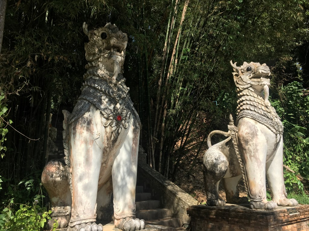 Two lion or dragon type statues at Wat Pha Lat, a temple in the mountains of Chiang Mai, Thailand.