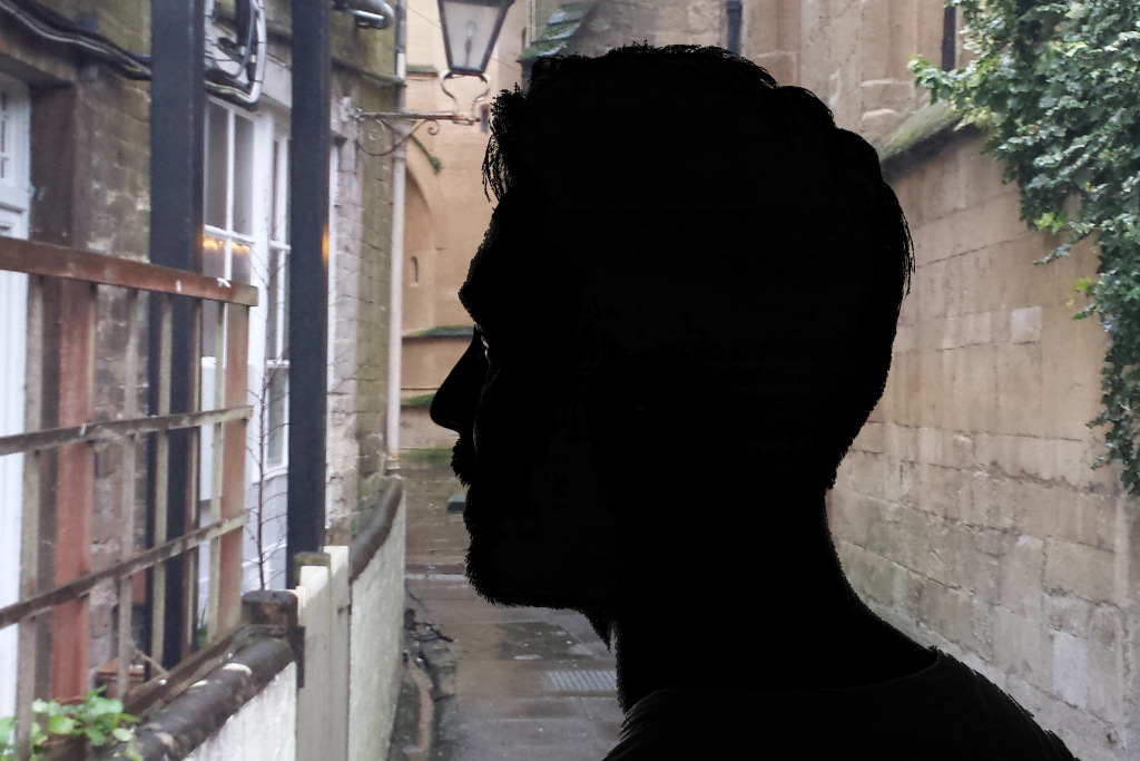 Silhouette of a man standing in a narrow alley with a cotswold stone wall of a building behind on right and windows of shops to the left