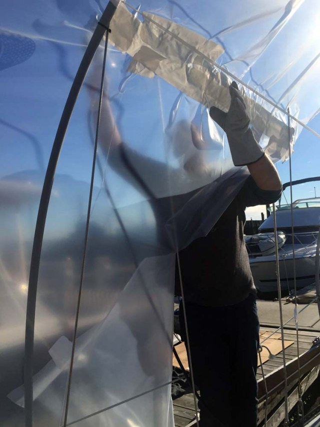 Shrinkwrapping a sailboat in the water with the mast up