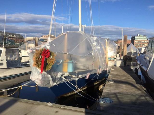 Door into shrinkwrap bubble sailboat in Maine winter