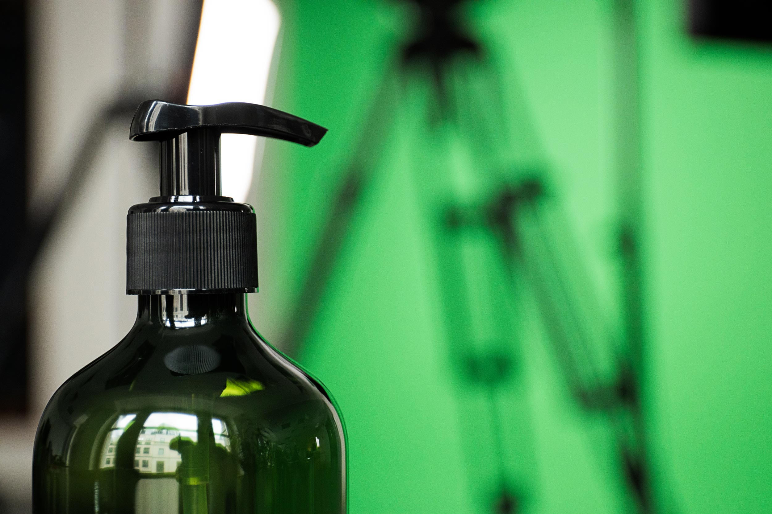 Close-up photograph of a bottle of hand sanitiser against a green screen backdrop.