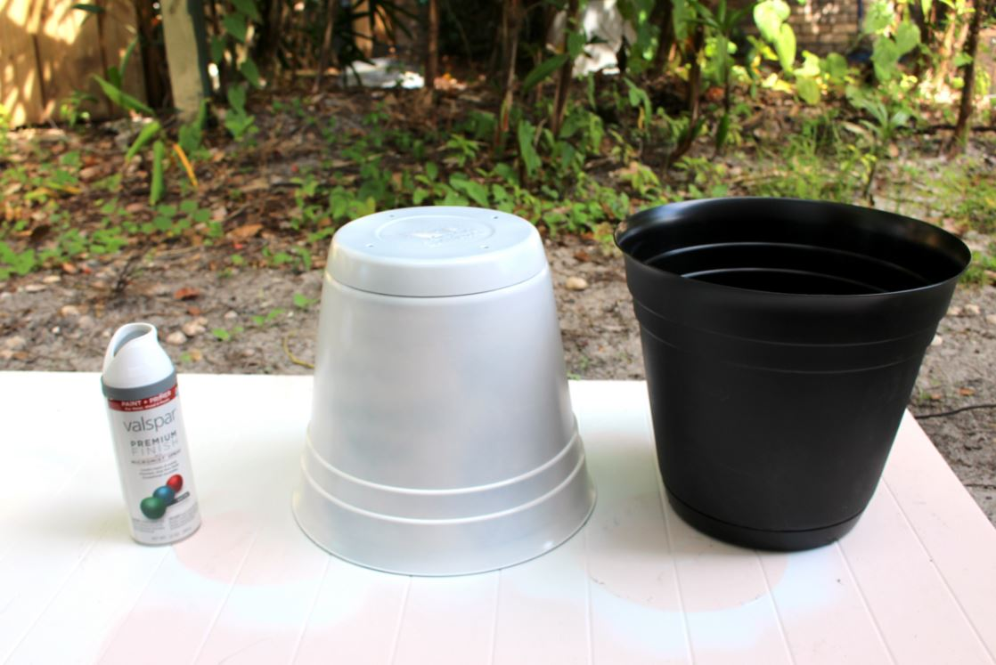 Spray painting plant pots white.