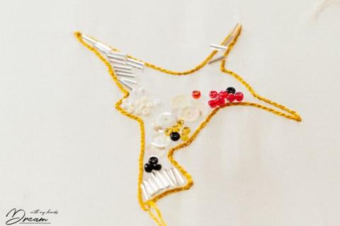 A hummingbird embroidery in progress.