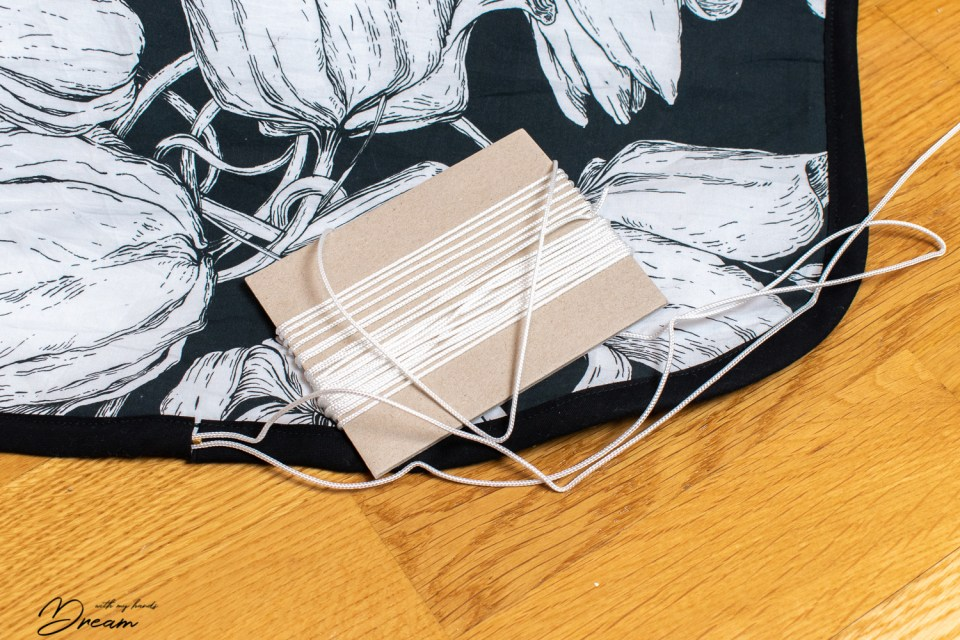 The cord is threaded through the gap in the bias binded edge of the ironing board cover.