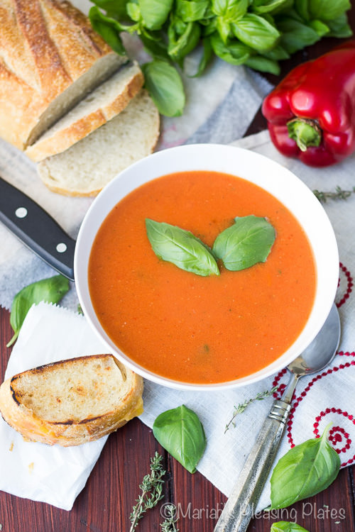 Easy Roasted Red Pepper and Tomato Soup filled with fresh herbs, fire roasted tomatoes, garlic and a splash of cream, this truly is the best tomato soup ever! The best part is that it only takes 25 minutes to make and is the best for winter since it uses sweet canned tomatoes!