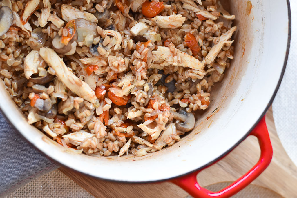 One Pot Farro with Chicken and Tomatoes cooking in the dutch oven