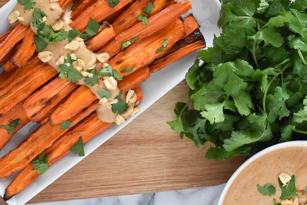 Roasted Carrots with Peanut Sauce on a white plate with cilantro