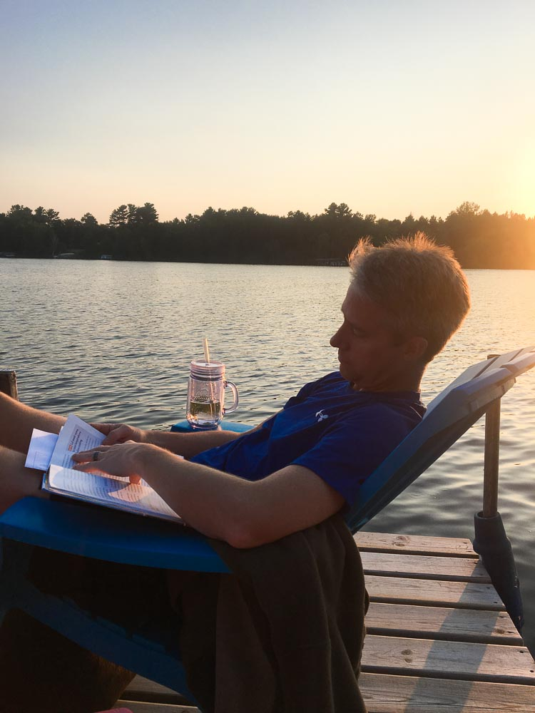 Reading on the dock at sunset