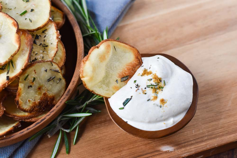 A Lemon Rosemary Potato dipped in a bowl of cumin sour cream