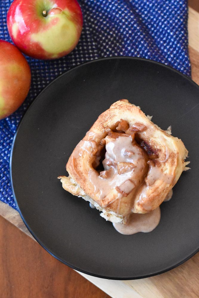 An overhead view of an apple cinnamon roll on a plate